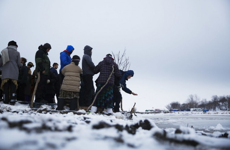 Bill Rack, of Wauwatosa, Wis., releases tobacco at the edge of the Cannonball river during a Native American water ceremony at the Oceti Sakowin camp where people have gathered to protest the Dakota Access oil pipeline in Cannon Ball, N.D., Friday, Dec. 2, 2016. According to Native American beliefs, tobacco is used to open a barrier between the physical and the spiritual worlds. (AP Photo/David Goldman)