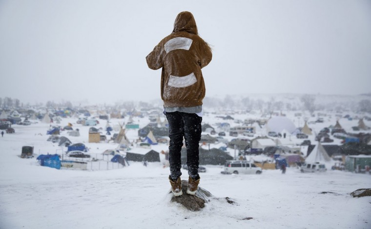 "In this Tuesday, Nov. 29, 2016 photo, Damin Radford, of New Zealand, looks out over the Oceti Sakowin camp where people have gathered to protest the Dakota Access pipeline in Cannon Ball, N.D. ""It's the right thing to do isn't it?"" said Radford of coming to the camp. ""It's symbolic of alot of things in the planet and this is the unification of people standing up for it."" (AP Photo/David Goldman)"