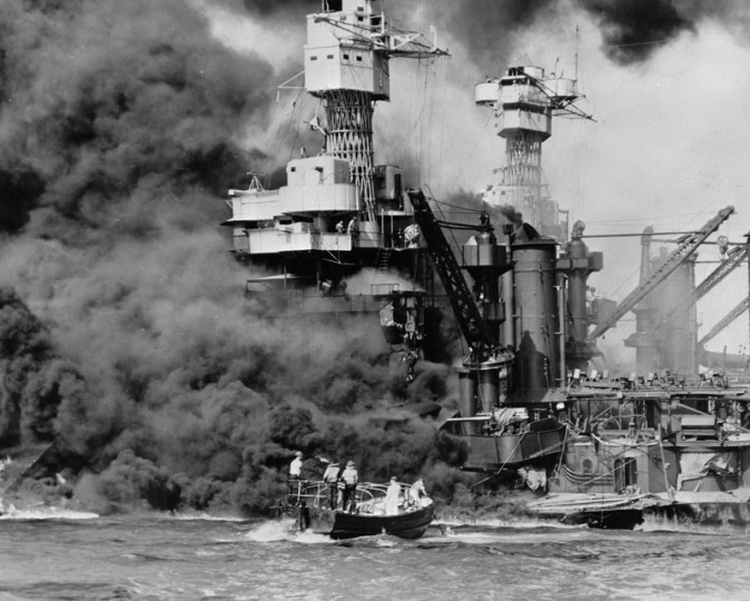 In this Dec. 7, 1941, photo made available by the U.S. Navy, a small boat rescues a seaman from the USS West Virginia burning in the foreground in Pearl Harbor, Hawaii, after Japanese aircraft attacked the military installation. (U.S. Navy via AP, File)