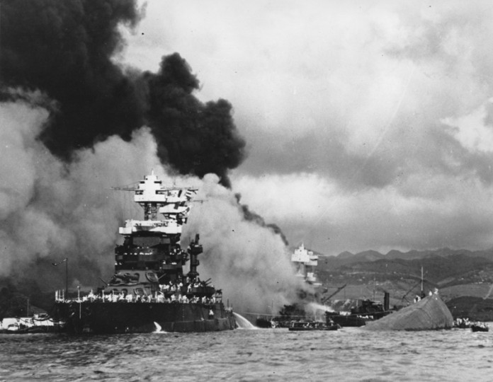 In this Dec. 7, 1941, file photo, part of the hull of the capsized USS Oklahoma is seen at right as the battleship USS West Virginia, center, begins to sink after suffering heavy damage, while the USS Maryland, left, is still afloat in Pearl Harbor, Oahu, Hawaii. (AP Photo/U.S. Navy, File)