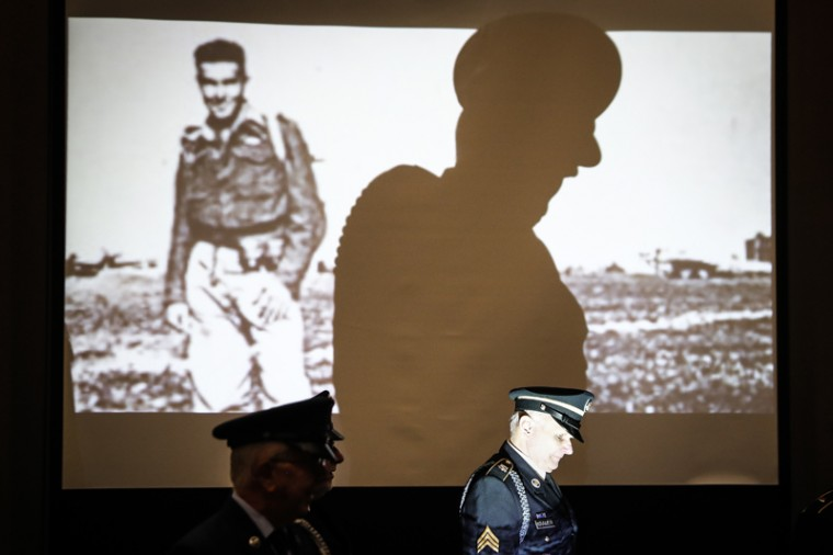 Honor guard members pass a projection of old photos depicting American soldiers during a ceremony at the Sharonville Convention Center to commemorate the 75th anniversary of the Dec. 7, 1941 attack on Pearl Harbor, Wednesday, Dec. 7, 2016, in Cincinnati. (John Minchillo/AP)
