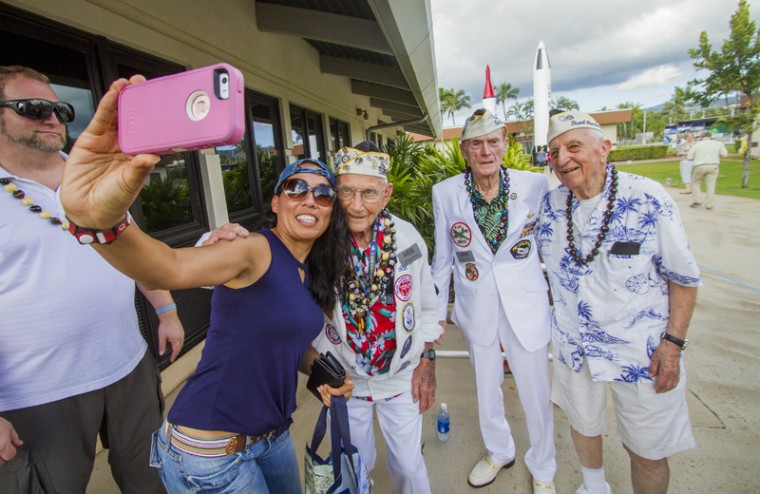 "About 30 Pearl Harbor Survivors with the ""Greatest Generation"" vets meet and greet with visitors at the Pearl Harbor Visitor Center Monday in Honolulu. At left, Bianca Coronado takes a selfie with Pearl Harbor survivors from left, Stuart ""Stu"" Hedley, Jack Holder and Ed Stone. (Dennis Oda/The Star-Advertiser via AP)"