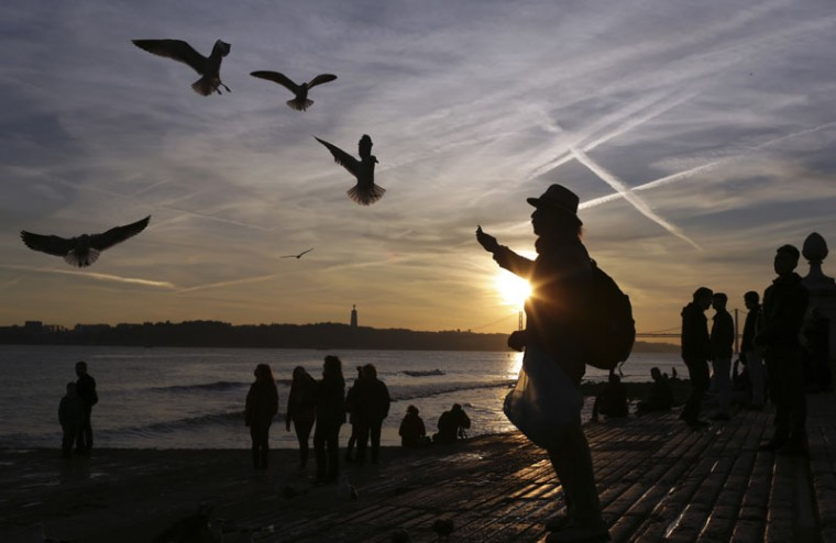 A man feeds pieces of bread to seagulls by the Tagus river bank in Lisbon, Portugal, as the sun sets Wednesday, Dec. 21 2016. The winter solstice of 2016 occurs on Dec. 21 marking the shortest day and longest night of the year in the northern hemisphere. (Armando Franca/AP)
