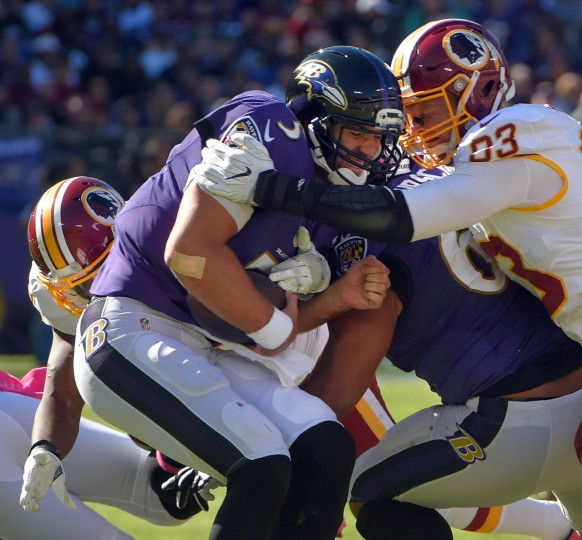Baltimore, MD -- 10/09/2016 -- Washington Redskins linebacker Terence Garvin (behind) and defensive end Trent Murphy (93) combine to drill Baltimore Ravens quarterback Joe Flacco (5) who is sacked for an 18-yard loss during the third quarter in Baltimore. The Ravens imploded, 16-10. (Karl Merton Ferron / Baltimore Sun)