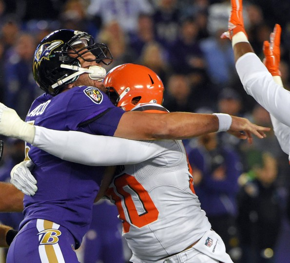 Baltimore, MD -- 11/10/2016 -- Baltimore Ravens quarterback Joe Flacco gets crushed by Cleveland Browns DL/LB Emmanuel Ogbah while passing during the first quarter in Baltimore. (Karl Merton Ferron / Baltimore Sun)