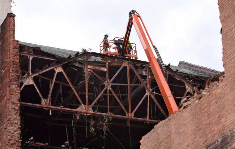Workers from NorthStar Construction dismantle the steel truss above the stage. The partial demolition of the Mayfair theater on N. Howard Street is nearing completion.   (Amy Davis/Baltimore Sun)