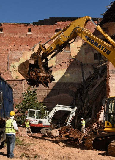 NorthStar Construction workers watch an excavator remove debris. The partial demolition of the Mayfair theater on N. Howard Street is nearing completion.   (Amy Davis/Baltimore Sun)