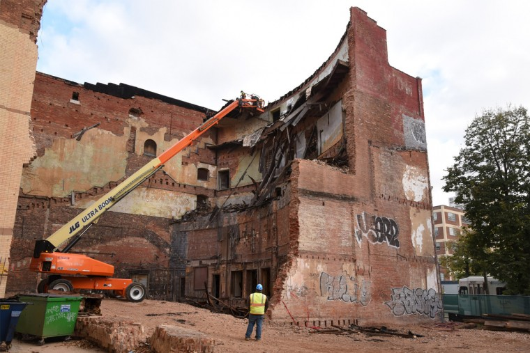 Workers in a man lift remove material near the front roof line of the theater. The partial demolition of the Mayfair theater on N. Howard Street is nearing completion.   (Amy Davis/Baltimore Sun)