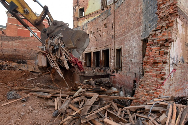 An excavator removes debris from the demolition process near the rear of the auditorium. The exit doors lead to the lobby. The partial demolition of the Mayfair theater on N. Howard Street is nearing completion.   (Amy Davis/Baltimore Sun)