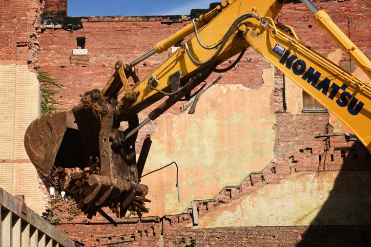 An excavator places debris into a dump truck for removal. The partial demolition of the Mayfair theater on N. Howard Street is nearing completion.   (Amy Davis/Baltimore Sun)