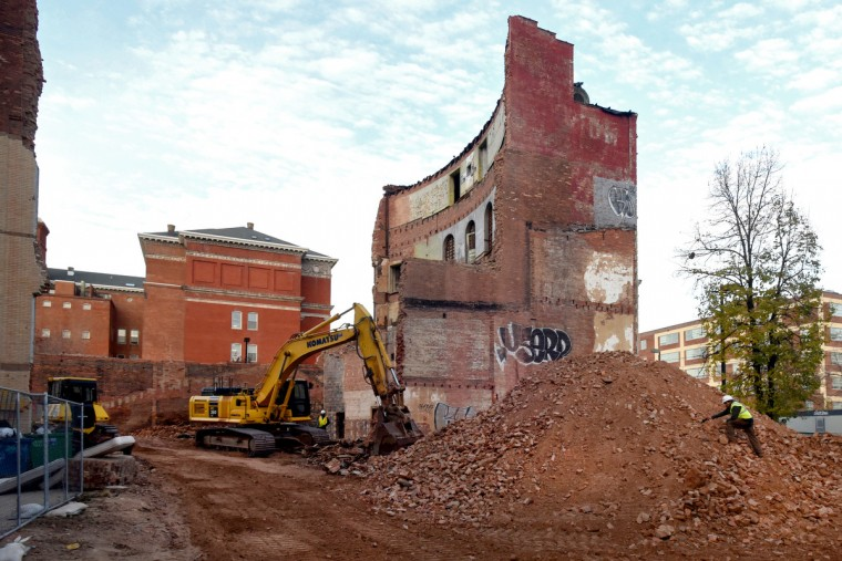 The partial demolition of the Mayfair theater on N. Howard Street is nearing completion.   A worker from K&K Adams Inc. climbs a mound of bricks that were taken down from the high brick walls. (Amy Davis/Baltimore Sun)