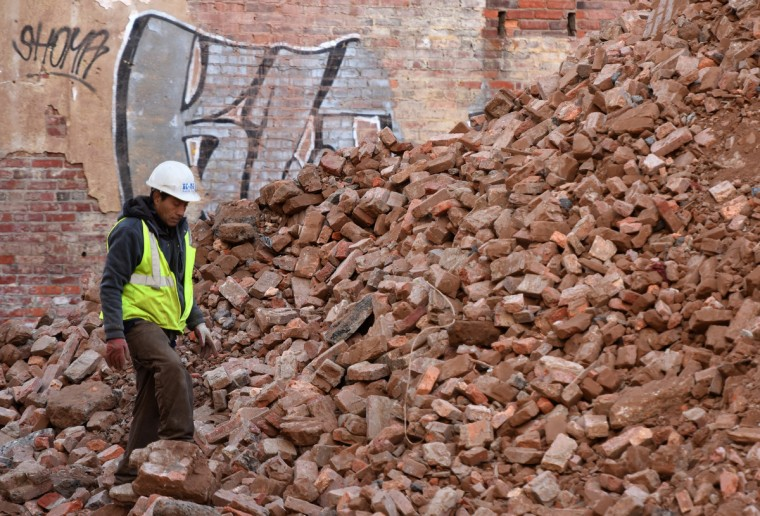 Umberto Reyes of K&K Adams, Inc., picks through the brick rubble from the rear walls of the Mayfair theater that have been knocked down. The bricks will be crushed and recycled. The partial demolition of the theater on N. Howard Street is nearing completion.  (Amy Davis/Baltimore Sun)