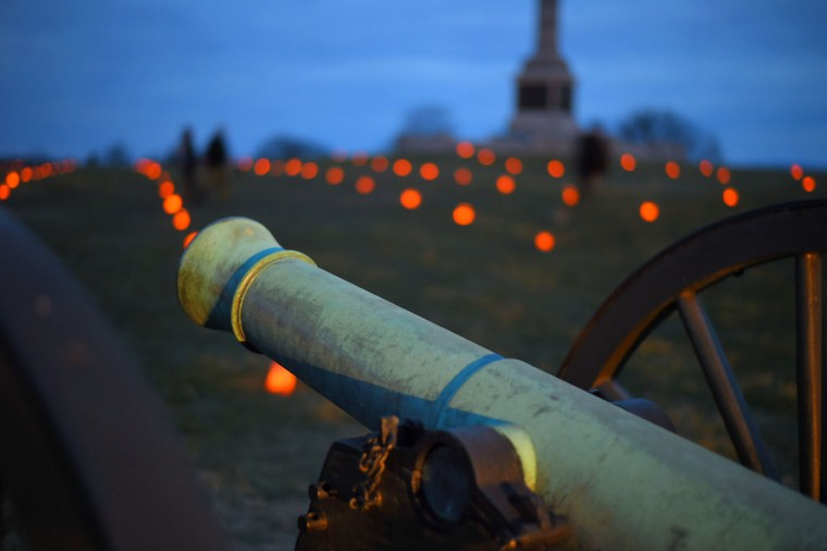 A cannon is illuminated by a vehicle's headlights while luminaries glow during the 28th Annual Memorial Illumination of over 23,000 luminaries at Antietam National Battlefield. (Karl Merton Ferron/Baltimore Sun)
