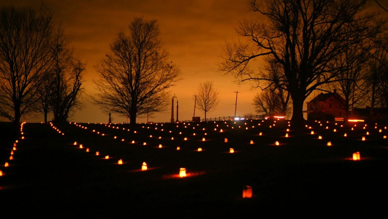 Trees are silhouetted against the night sky as vehicles slowly crawl south along historic Hagerstown Pike during the 28th Annual Memorial Illumination of over 23,000 luminaries at Antietam National Battlefield. (Karl Merton Ferron/Baltimore Sun)