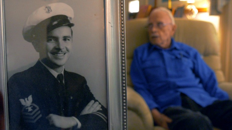 A portrait of Robert Van Druff is in foreground while the elder speaks about his experience aboard the destroyer USS Aylwin when it was attacked 75 years ago, on Dec. 7, 1941, sparking U.S. involvement in World War II. (Karl Merton Ferron/Baltimore Sun)