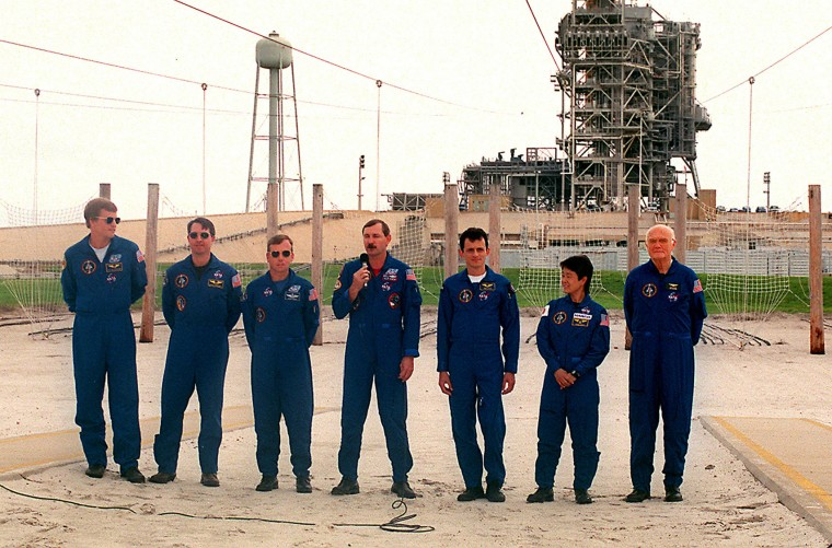 From left, Scott Parazynski, Stephen Robinson, Steven Lindsey, Curt Brown, Pedro Duque, Chiaki Mukai and John Glenn, crew of the historic Oct. 29, 1998 Discovery shuttle launch, pose for a picture at Kennedy Space Center on Oct. 8. (Red Huber/Orlando Sentinel/TNS)