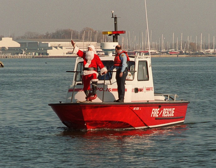 Santa greets children of all ages at the Annapolis City Dock in 2001. Al Hopkins, white-haired, blue-eyed and beardless,  portrayed Jolly Old St. Nick in a tour around Annapolis on Friday. The city's fire boat delivered him to the City Dock. He then boarded a fire engine and visited other sites in the city. (Jed Kirschbaum/Baltimore Sun)