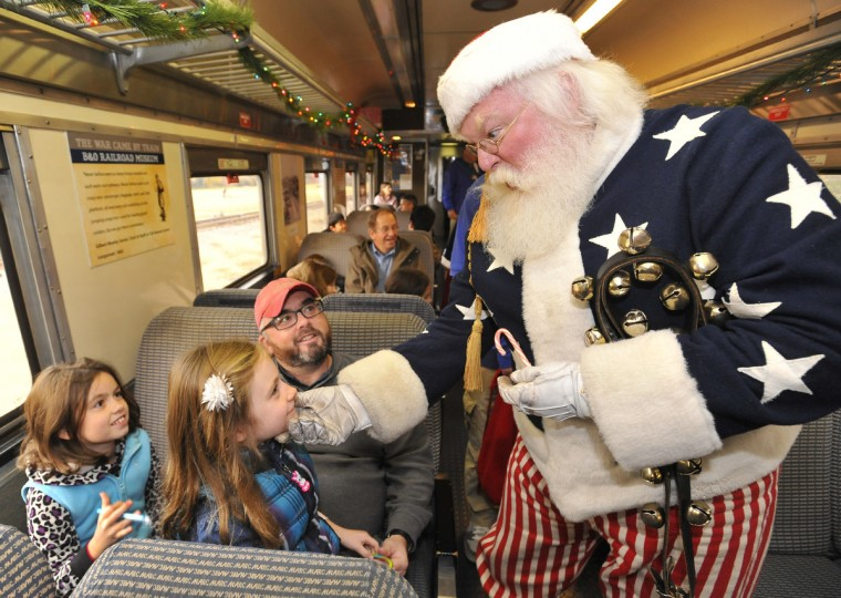 Santa, played by Kevin Rawlings of Hagerstown, greets Sara Murnane, 6, second from left, as her sister Katie, 9, left, and father Rich Murnane look on during a train trip aboard the Mt. Clare Express  during the Holiday Festival of Trains and Toys at the B&O Railroad Museum in 2012. (Amy Davis/Baltimore Sun)