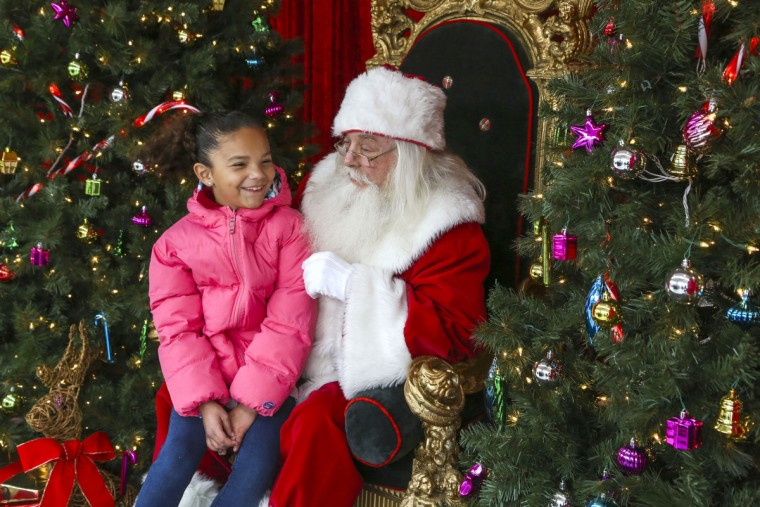 Santa Claus discuss art supplies with Hannah Mitchell, 8. The popular Santa House at Harborplace has moved to a new location, right next door to Ripley's Believe It or Not Museum in 2015. (Kaitlin Newman/Baltimore Sun)