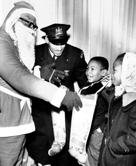"Creston ""Doc"" Woingust, dressed as one of Santa's helpers, and patrolman Alfred C. Smith,  give stockings to a brother and sister, Everett, 8, and Wanda Loggins, 7,  at the 1963 Western District Christmas party that was held at the old Royal Theater on Pennsylvania Avenue in 1963. (William l Laforce Jr./Baltimore Sun)"