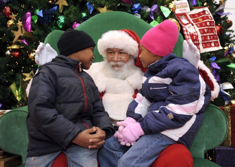 Luke Durant, who has been Santa Claus at the Mondawmin Mall for over 20 years,  listens to the Christmas wishes of Breon Griffin, 7, left, and his sister Brianna Griffin, 8 in 2009. (Barbara Haddock Taylor/Baltimore Sun)