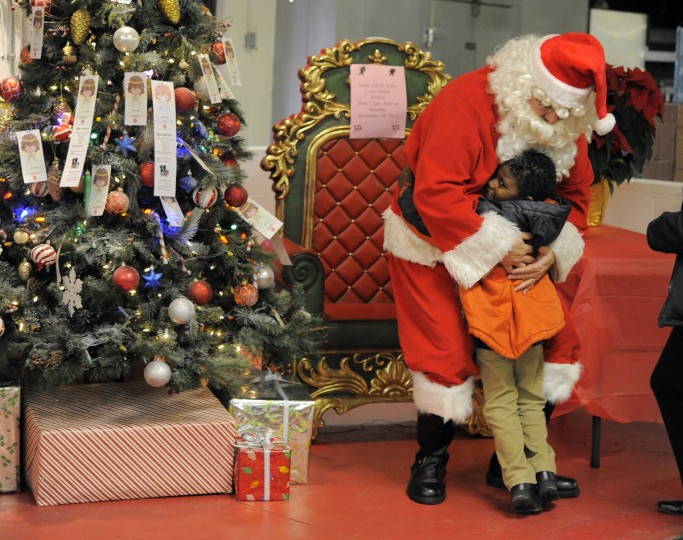 Michael Jones, 5, of Federal Hill Preparatory School gives Santa a big hug at the Cross Street Market. The Merchants Association of Cross Street Market invited Pre-K students to the market to visit Santa in 2013. (Lloyd Fox/Baltimore Sun)