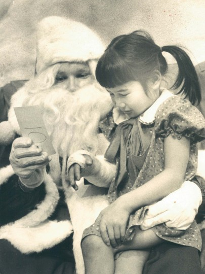 In 1979, Santa (Tom Brzeznaski) reads list of little Maura Dolon (6) at the Columbia Mall.  She broke her arm on the monkey bars, but Santa promised her a good Christmas. (Clarence B. Garrett/Baltimore Sun)