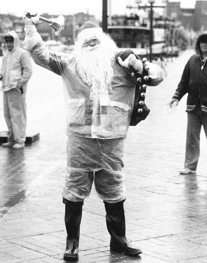 Santa rings a bell and passes out candy on the seawall in Inner Harbor in the rain in 1977.  (Weyman Swagger/Baltimore Sun)