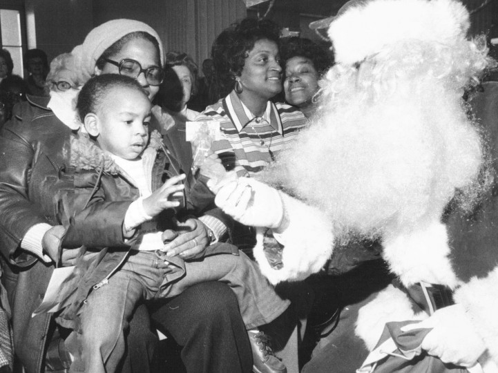 "Young Bert Roberts reaches for candy from Santa Bill Fogel at the opening of the city's ""mitten tree program"" in the Municipal Building in 1977.  The public is invited to bring pairs of mittens of gloves to hang on the tree located there.  The gloves will be taken off the tree and given to poor children on Christmas Eve by the Salvation Army.  (Ralph L. Robinson/Baltimore Sun)"