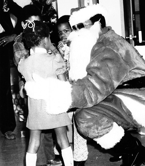 Santa's twinkling eyes were behind sunglasses yesterday - maybe from too much glare at the North Pole - at the annual Department of Social Service Christmas party, but that did not stop the youngsters from getting close to the old folk hero and telling him their most secret wishes in 1977.  (William H. Mortimer /Baltimore Sun)