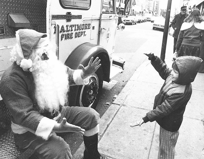Tony Peddicord, 5, shows Santa Claus the size of the bicycle he wants for Christmas in 1980.  Firefighter Stanley Leonard played Santa near the Cross Street Market for a department promotion stressing fire safety during the holidays.  (Walter McCardell/Baltimore Sun)