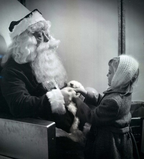 In a custom that seems to be peculiar to Baltimore, one of his visitors gives Santa a penny in 1957.   Santa is Warren Lee Terry.  (Richard Stacks/Baltimore Sun)