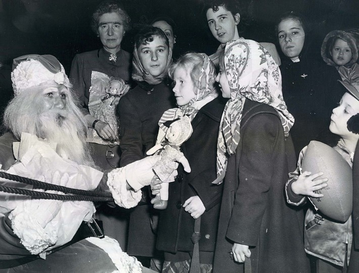 Santa Claus (Raymond Roberston) give kids gifts at the 5th Regiment Armory in 1951. (Joseph DiPaola/Baltimore Sun)