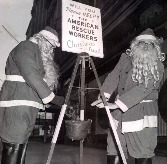 A pair of Santas warm their hands while collecting for the American Rescue Workers Christmas Fund at the corner of Howard and Lexington in 1958. (Clarence Garrett/Baltimore Sun)