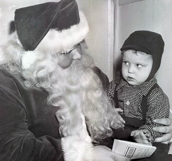 A young child gives Santa a questioning look in 1952. (George Cook/Baltimore Sun)