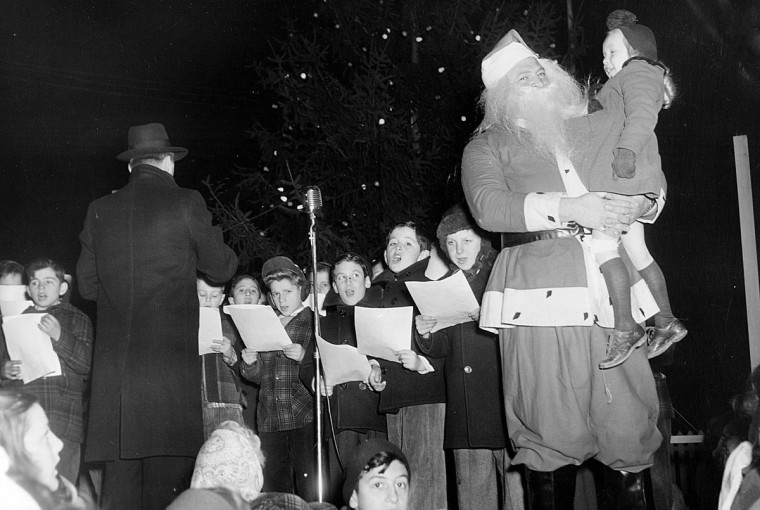Santa holds a child as St. Ambrose carol singers perform at Pimlico in 1947. (Frank Miller/Baltimore Sun)