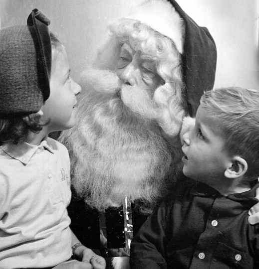 At one of the big downtown department stores in 1957, Santa Claus hears what two children would like for Christmas.  He is Warren Lee Terry, a former Santa and actor for eight years.  (Richard Stacks/Baltimore Sun)