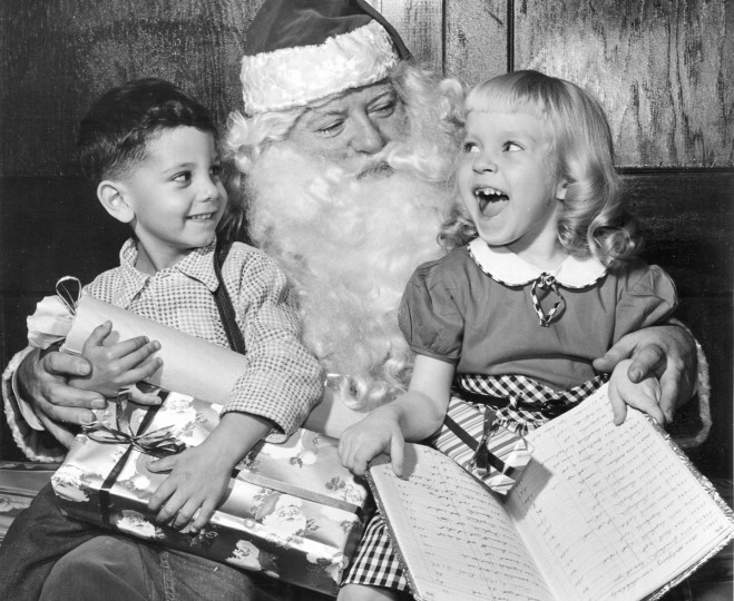 Jerry Wood, 4-years-old and Nancy Brown, 5-years-old look for their names on Santa's Golden Book, which lists children who have been nice in 1955.  Santa is John Bowers.  (Richard Stacks/Baltimore Sun)