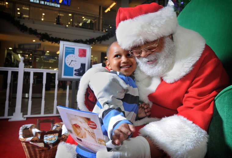 Santa Claus (Luke Durant) gives a hug to Nathaniel Thomas, Jr., almost three at Mondawmin Mall in 2013. (Algerina Perna/Baltimore Sun)