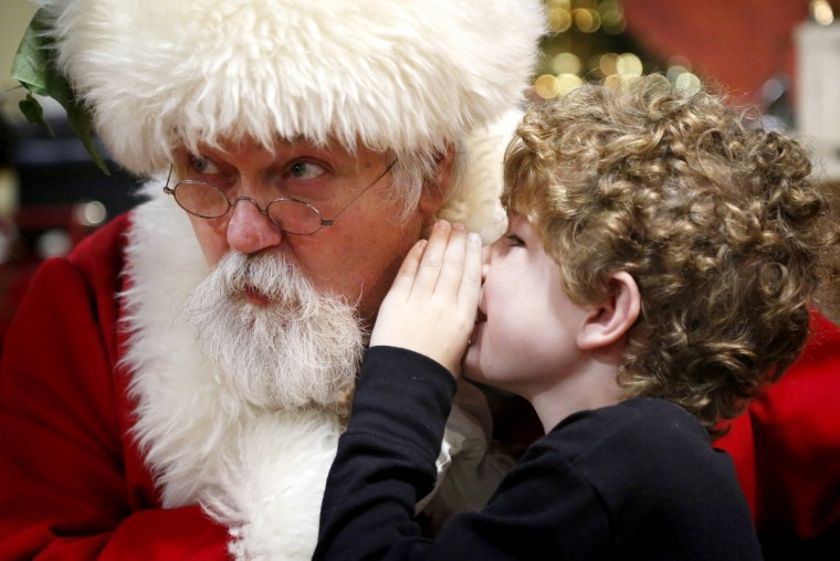 "Will Holloway, 8, tells Santa that he wants a ""small puppy Dalmatian"" for Christmas at the Fire Museum in 2014. (Cassidy Johnson/Baltimore Sun)"