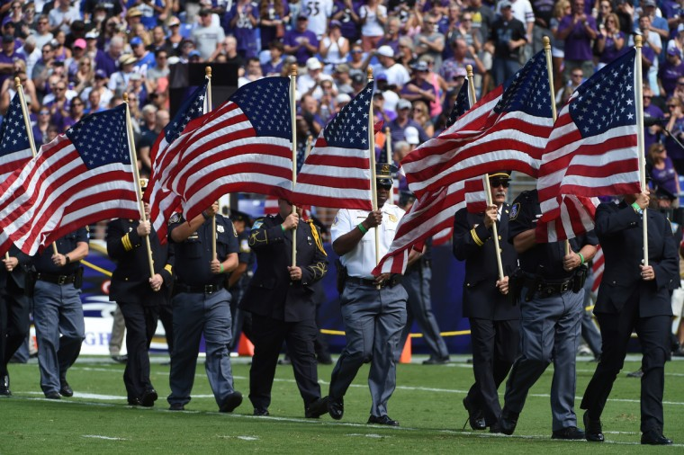 Baltimore, MD.--9/11/16-- First responders march onto the field with the Stars and Stripes during Ravens' 2016 season opener at M & T Bank Stadium. (Kenneth K. Lam/Baltimore Sun)