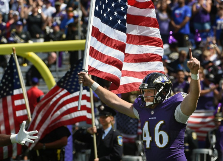 Baltimore, MD.--9/11/16-- The Ravens' Morgan Cox hoists the Stars and Stripes during the 2016 season opener at M & T Bank Stadium. (Kenneth K. Lam/Baltimore Sun)