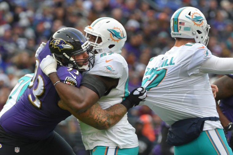 Baltimore, Maryland--12/4/16--  Ravens' #93 Lawrence Guy gets a fist full of Dolphin quarterback Ryan Tannehill's jersey while being blocked by Dolphins' #67 Laremy Tunsil in the  first half.  (Lloyd Fox/Baltimore Sun)