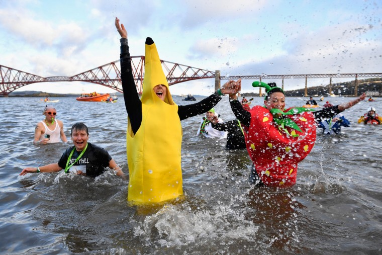 SOUTH QUEENSFERRY, SCOTLAND - JANUARY 01:  Members of the public dressed as a banana and a strawberry splash around in the water as they join around 1,000 New Year swimmers, many in costume, in front of the Forth Rail Bridge during the annual Loony Dook Swim in the River Forth on January 1, 2017 in South Queensferry, Scotland. Tens of thousands of people gathered last night in Edinburgh and other events across Scotland to see in the New Year at Hogmanay celebrations.  (Photo by Jeff J Mitchell/Getty Images)