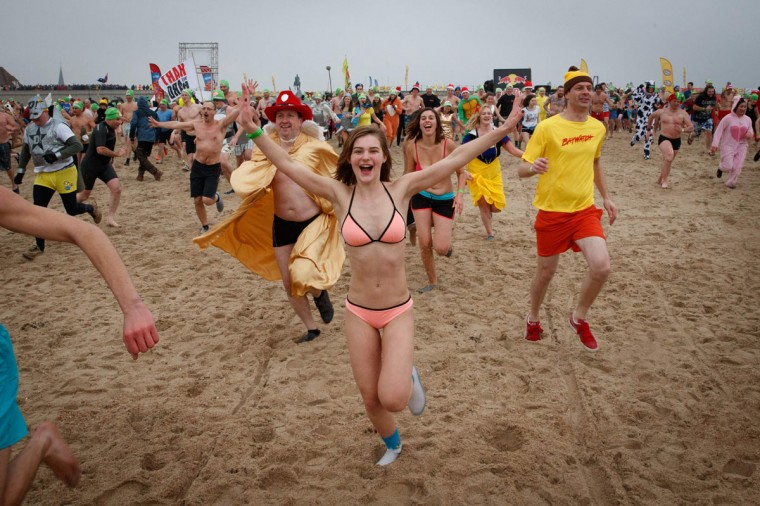 People run down the beach during the traditional New Year's dive (Nieuwjaarsduik) into the North Sea, in Oostende, on January 1, 2017. (AFP PHOTO / Belga / KURT DESPLENTER)