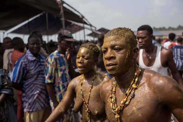 Voodoo devotees covered in oil, powder and yellow colorant are seen at the annual Voodoo Festival on January 10, 2017 in Ouidah. (STEFAN HEUNIS/AFP/Getty Images)