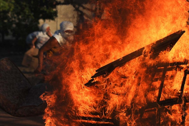 "Women relatives of inmates set makeshift barricades on fire in protest for the transfer of some 200 prisoners from the Alcacuz Penitentiary Center to other prisons in Rio Grande do Norte, Brazil on January 18, 2017. Brazilian authorities said Wednesday they are deploying 1,000 troops to ""clean out"" arms and cellphones from restive prisons while police moved to end a deadly gang face-off in one northern penitentiary. (ANDRESSA ANHOLETE/AFP/Getty Images)"