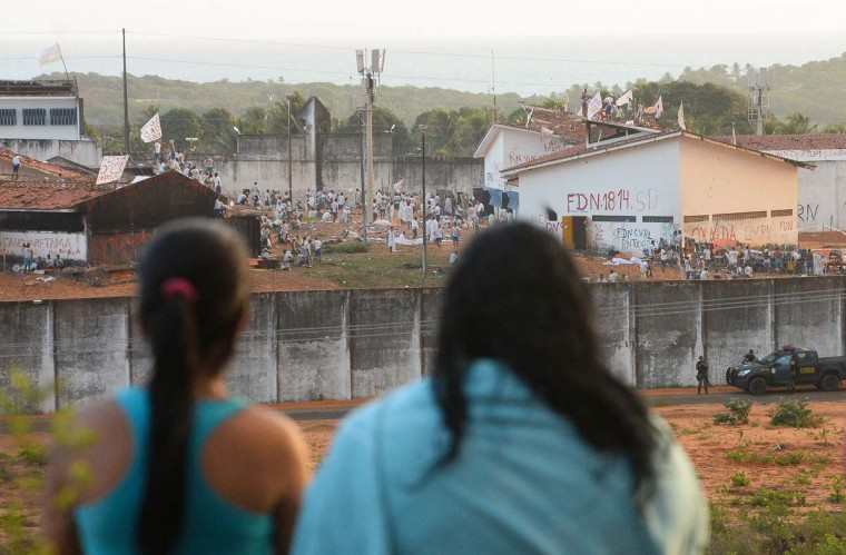 Relatives of detainees look at the Alcacuz Penitentiary Center during a riot in Rio Grande do Norte, Brazil on January 18, 2017.  Brazil's government on January 17 ordered the armed forces to help secure the country's overcrowded jails as police fought to separate rival gangs of inmates in one prison following a massacre. (ANDRESSA ANHOLETE/AFP/Getty Images)