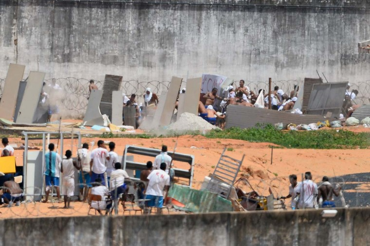 Prisoners cover themselves using makeshift shields as riot police agents (out of frame) fire rubber bullets during a rebellion at the Alcacuz Penitentiary Center near Natal in Rio Grande do Norte, Brazil on January 17, 2017.  Brazilian police fired rubber bullets Tuesday at inmates who have taken over a jail where dozens were massacred over the weekend in the latest in a string of prison riots. Police positioned on top of the outer walls of the Alcacuz jail near the northeastern city of Natal fired at a crowd of inmates who had taken control of part of the complex. A total of 26 prisoners were killed in Alcacuz -- many of them beheaded -- during a violent riot that broke out late Saturday, according to officials. (ANDRESSA ANHOLETE/AFP/Getty Images)