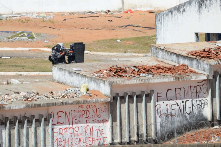 "Members of the special police battalion enter the Alcacuz Penitentiary Center to regain control of the penitentiary in Rio Grande do Norte, Brazil, on January 18, 2017. Brazilian authorities said Wednesday they are deploying 1,000 troops to ""clean out"" arms and cellphones from restive prisons while police struggled to end a deadly gang face-off at Alcacuz. The soldiers were being brought in to respond to a ""national emergency"" in the badly overcrowded prison system, Defense Minister Raul Jungmann said. (ANDRESSA ANHOLETE/AFP/Getty Images)"